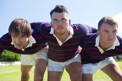 Close up of rugby players bending while standing at field