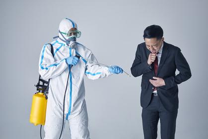 消毒をする防護服を着用した男性と日本人ビジネスマン