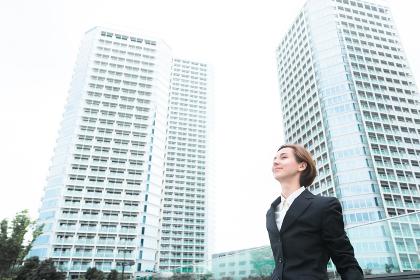 高層ビルを前にリラックスする女性