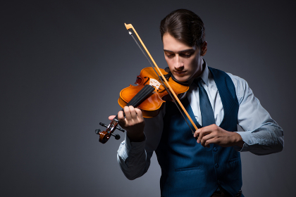 Young man playing violin in dark room