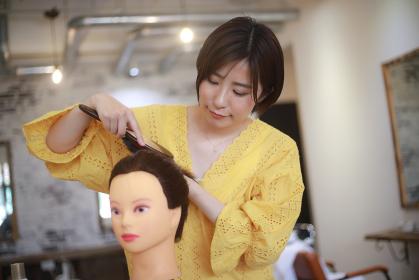 髪を整える練習をする美容師