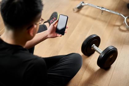 スマートフォンでトレーニングアプリを見るアジア人男性