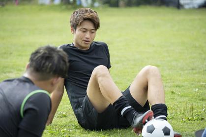 公園でサッカーをする若い男性