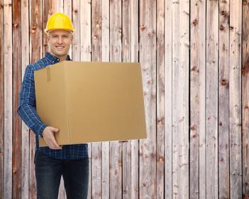 smiling male builder in helmet with cardboard box