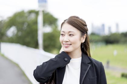 髪を押さえる女性(ビジネスイメージ)