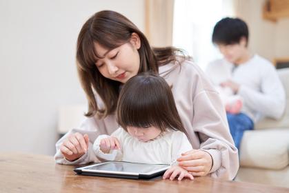 ママと一緒にでタブレットを見るアジア人の女の子