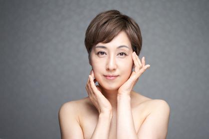 両手で顔の潤いを確かめる中年の日本人女性