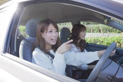 友達とドライブをしながら指差す女性