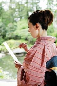 筆で俳句を書く着物を着た女性