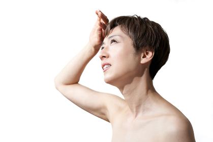 強い日差しを受ける中年の日本人女性