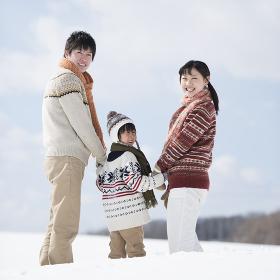 雪原で手をつなぐ家族