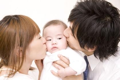 両親にキスをされる赤ちゃん