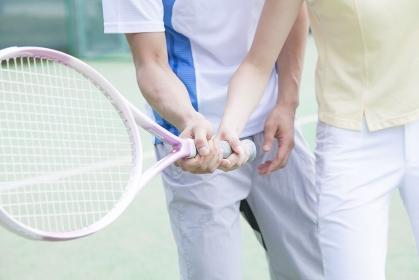 テニスレッスンをする男女