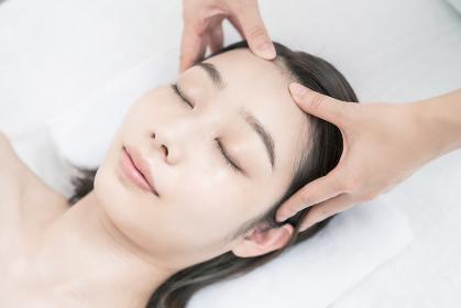 エステサロンで頭部をマッサージされる若い女性