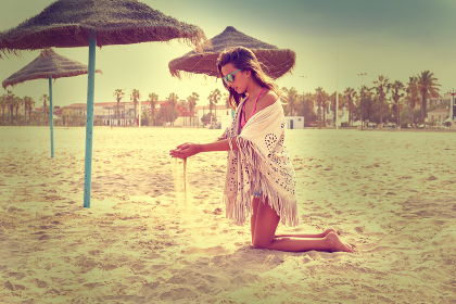 Teen girl on the beach playing with sand near thatch umbrellas filtered image