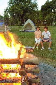 キャンプファイヤーを見るカップル
