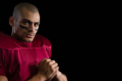 Determined American football player against a black background