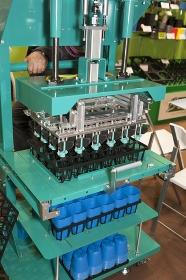 ビニールの植木鉢をトレーにセットする機械