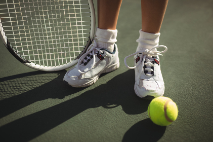 Low section of girl with racket and tennis bal