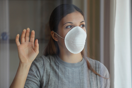 COVID-19 Pandemic Coronavirus Woman Quarantine Home Isolation Wearing Mask Protective Waiting End of Pandemic SARS-CoV-2. Girl face mask against Coronavirus Disease 2019 looking through the window.
