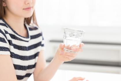 部屋で水を飲む女性 手元