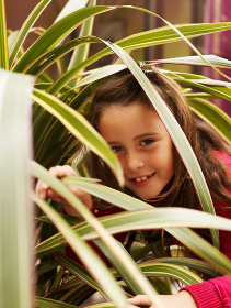 Girl peering through leaves of plant