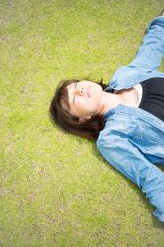 芝生で気持ちよさそうに寝る女性