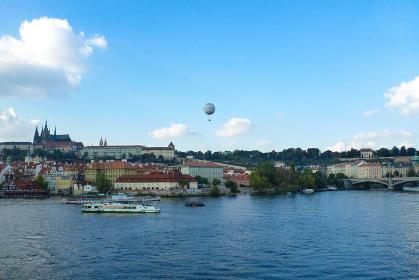 チェコ・プラハ市街地にてモルダウ川の眺望と上空を飛ぶ熱気球