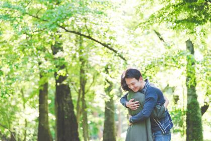 新緑の中、抱き合うカップル