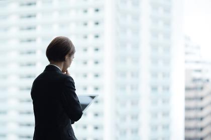 タブレットPCを使用する女性・都市風景バック