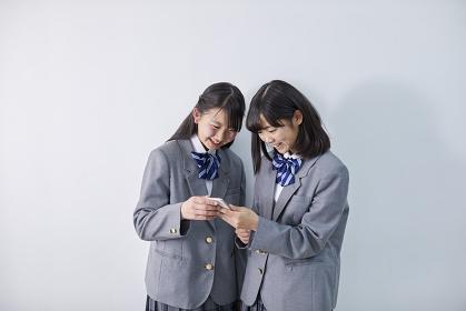 スマートフォンを見て笑う女子中学生