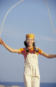 Maedchen mitbraunen Zoepfen und gelbem Kopftuch, 12 Jahre, bekleidet mit orange farbenem Polo Shirt und kurzer weisser Latzhose springt bei strahlend blauem Himmel am Strand Seilchen