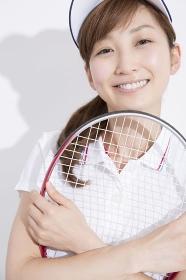テニスラケットを持って微笑む女性