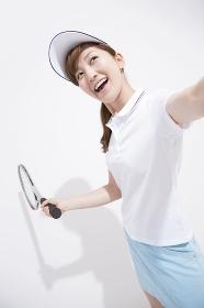 テニスラケットを振る女性