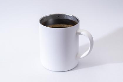コーヒーの入った保温性のある白いマグカップ
