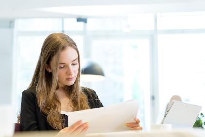オフィスで資料を確認する白人の女性