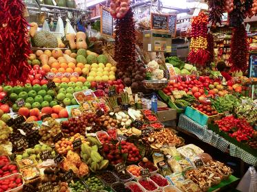 スペイン・バルセロナの市場にて新鮮なフルーツと野菜が並ぶ生鮮食品店の様子