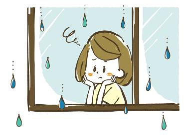 雨の日に憂鬱そうに窓の外を眺める女性