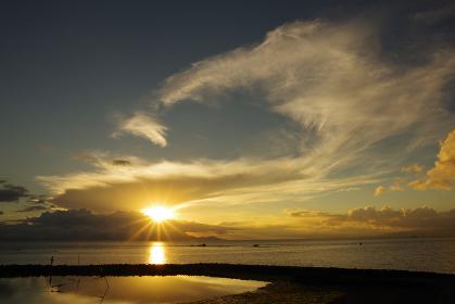 雲の合間から昇る太陽