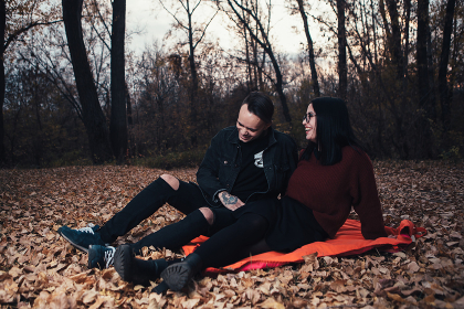 young man and young woman are sitting on a plaid in an autumn forest