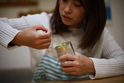 缶詰が開けられず指が痛む女性