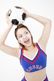 サッカーボールを頭に乗せるチアガール