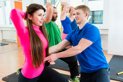 Men and women in gym doing pilates workout
