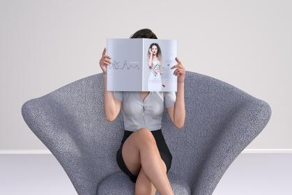 1人がけのソファーに座り足を組むビジネス女子がファッション誌を読む姿