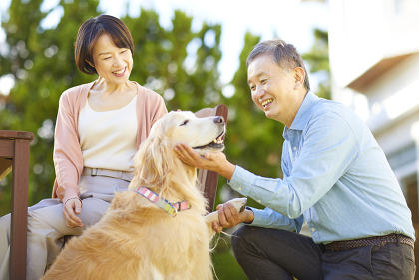 テラスで犬と遊ぶ日本人シニア夫婦