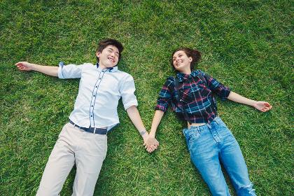 芝生に寝転がる若いカップル(欧米人・アジア人)