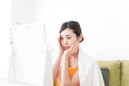 部屋でスキンケアをする若い女性