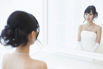 鏡の前に座るウエディングドレス姿の女性