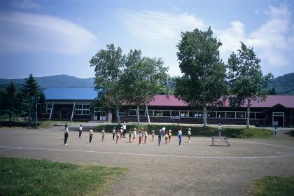 木造校舎と校庭で整列する生徒たち