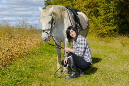 young rider girl with her white horse